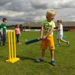 Blond haired 2nd Innings LW boy holding bat next to yellow stumps