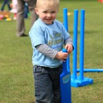 Young Boy Toddler in Blue LW T Shirt holding LW branded Bat against Grass