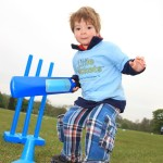 Upward Angled Picture of Boy in Blue Little Wickets Tee holding a LW branded cricket bat next to stumps