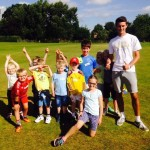Little Wickets Camp Children Outside with Coach All Thumbs Up