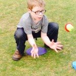 Little Wickets Camp Picture Young Boy with Glasses Crouching to Catch a Red & Green soft ball