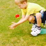 Young Boy in Yellow Crouching to Catch Red & Green Ball
