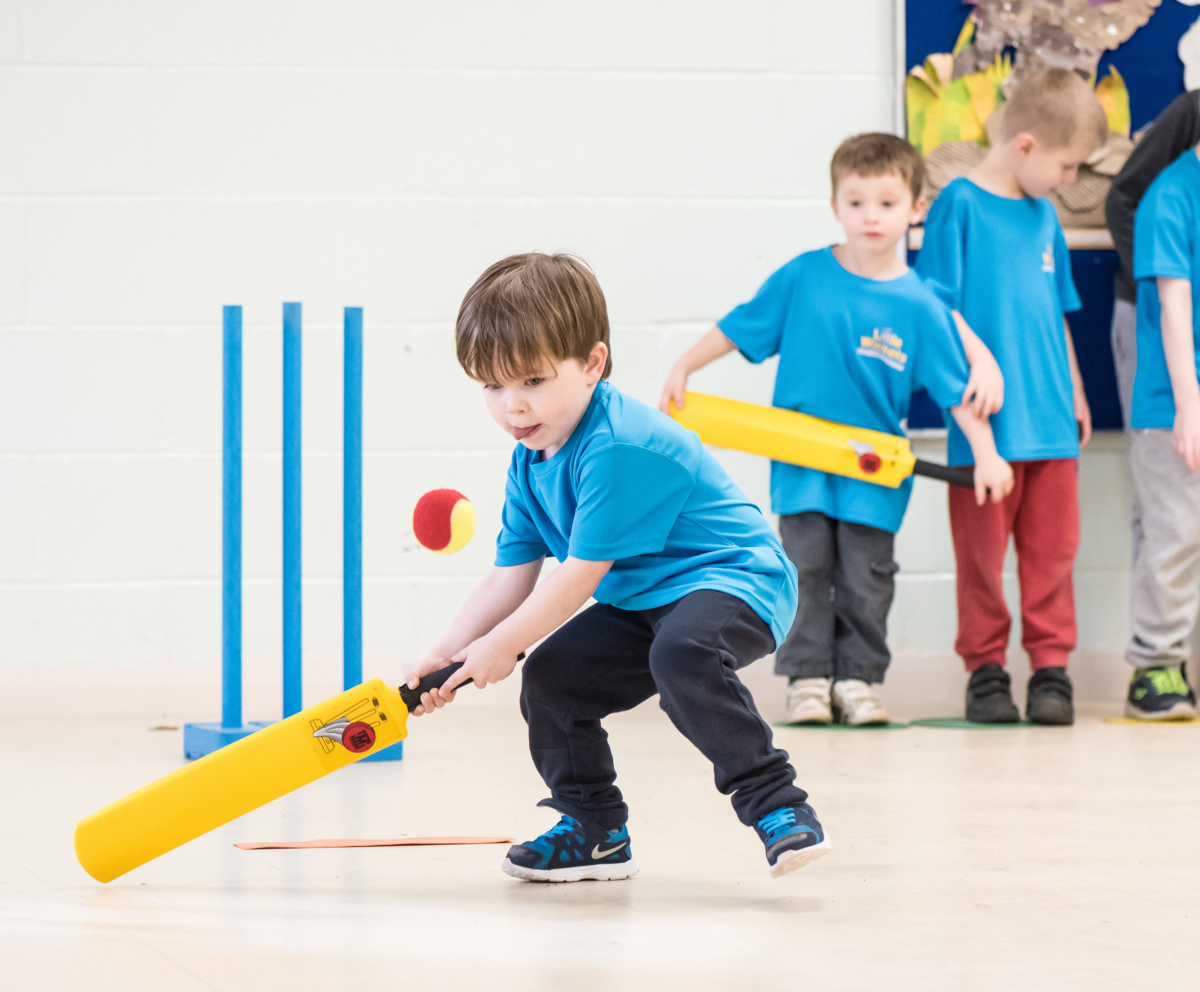 Young Boy in Bright Blue Little Wickets Top Playing Cricket